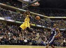 Indiana Pacers guard Paul George (L) flies past the basket after dunking the ball in front of Memphis Grizzlies forward Darrell Arthur during the fourth quarter of their NBA basketball game in Indianapolis, Indiana December 31, 2012. REUTERS/Brent Smith