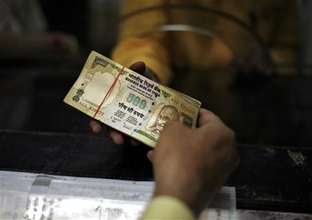 A man deposits his money in a bank in the northern Indian city of Amritsar April 19, 2010. REUTERS/Yasir Iqbal/Files