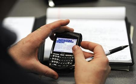 A person checks his Blackberry during a ''job club'' in Olathe, Kansas February 25, 2009. REUTERS/Dave Kaup/Files