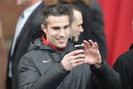 Manchester United player Robin Van Persie takes a photograph during the unveiling of a statue of Manchester United's manager Alex Ferguson at Old Trafford stadium in Manchester, northern England November 23, 2012. REUTERS/Nigel Roddis/Files