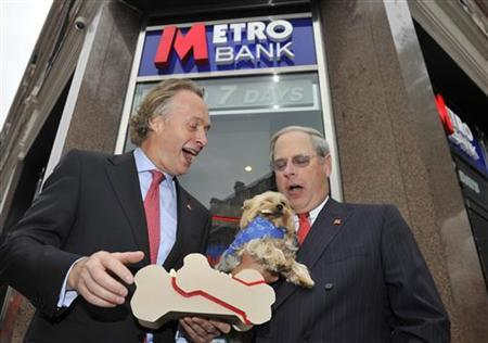 Chairman Anthony Thomson (L) and Vice Chairman Vernon Hill pose with a dog outside the first branch of Metro Bank in Holborn in central London July 29, 2010. REUTERS/Toby Melville
