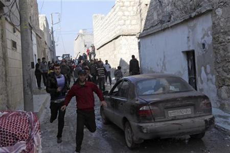 Residents run along a street after an air strike by a fighter jet loyal to Syrian President Bashar al-Assad in Aleppo's al-Marja district December 31, 2012. REUTERS/Muzaffar Salman