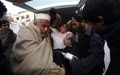 An injured driver (in white) who survived a shooting by unidentified gunmen in Swabi, arrives at the Lady Reading Hospital in Peshawar January 1, 2013. REUTERS/Fayaz Aziz