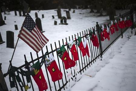 A U.S. flag hangs over stockings left as a memorial for victims of the Sandy Hook Elementary School shooting, along a fence surrounding the Sandy Hook Cemetery in Newtown, Connecticut December 27, 2012. REUTERS/Adrees Latif