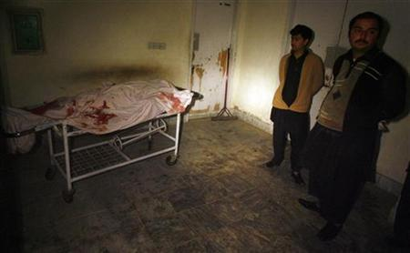 People stand near a body of an aid worker, who was killed by unidentified gunmen, at a hospital in Swabi January 1, 2013. REUTERS/Khuram Parvez