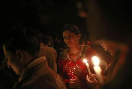 Demonstrators hold candles during a candlelight vigil for a gang rape victim who was assaulted in New Delhi December 30, 2012. REUTERS/Danish Siddiqui