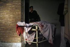 Policial é visto em frente a maca com o corpo de um assistente social morto por atiradores desconhecidos no Paquistão. Homens armados emboscaram e mataram seis assistentes sociais paquistanesas e um médico nesta terça-feira, segundo a polícia, e a entidade para a qual eles trabalhavam disse suspeitar que os ataques estão relacionados aos recentes assassinatos de funcionários de vacinação contra a pólio. 01/12/2013 REUTERS/Khuram Parvez