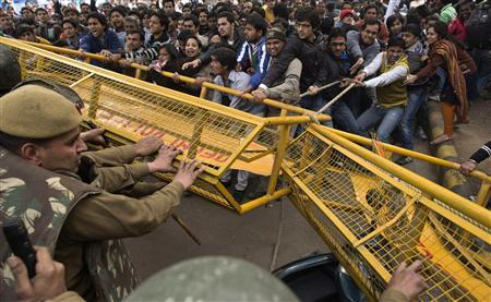 Demonstrators try to pull away a police barricade during a protest in New Delhi in this December 30, 2012 file photo. REUTERS/Ahmad Masood/File