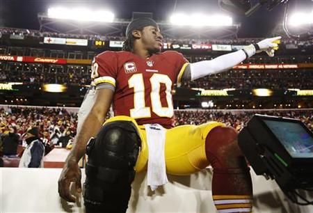 Washington Redskins quarterback Robert Griffin III (10) celebrates on the bench after his team beat the Dallas Cowboys during their NFL football game in Landover, Maryland December 30, 2012. REUTERS/Jonathan Ernst