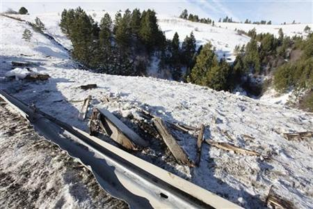 Twisted guard rail and debris line road side where tour bus careened off a mountain highway and plunged down a snow-covered slope, killing nine passengers and injuring at least 27 others, in Oregon December 31, 2012. REUTERS/Steve Dipaola