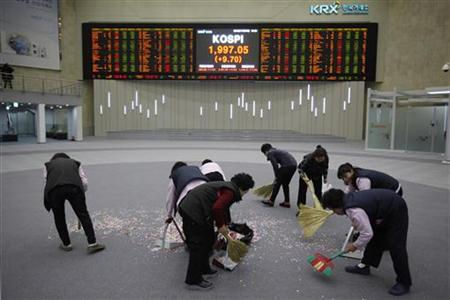 Workers sweep the floor in front of the final stock price index after the ceremonial closing event of the 2012 stock market during a photo opportunity for the media at the Korea Exchange (KRX) in Seoul December 28, 2012. REUTERS/Kim Hong-Ji