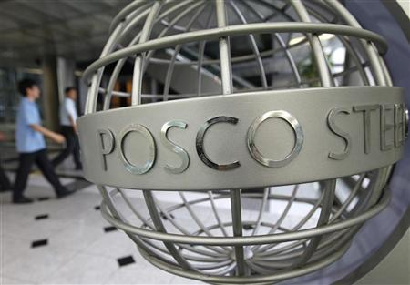 Employees of POSCO walk near a sculpture with POSCO's logo at the company's headquarters in Seoul July 22, 2011. REUTERS/Jo Yong-Hak