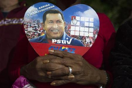 A supporter of Venezuelan President Hugo Chavez holds a picture of him, as she attends a ceremony in Caracas December 31, 2012. . REUTERS/Carlos Garcia Rawlins