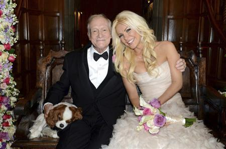 Octogenarian Playboy founder Hugh Hefner poses with his bride Crystal Harris and dog Charlie at their New Year Eve wedding at the Playboy Mansion in Beverly Hills, California in this handout photo taken on December 31, 2012. REUTERS/Elayne Lodge/PEI/Handout