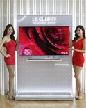 Models pose next to LG Electronics' organic light-emitting diode (OLED) television in Seoul January 2, 2013. REUTERS/Lee Jae-Won