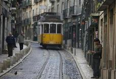 A man reads at a street of Mouraria neighbourhood in Lisbon December 3, 2012. Euro zone finance ministers will discuss the terms of the Greek debt buy-back at a meeting in Brussels on Monday and review a Cypriot bailout, though no decision on Cyprus is expected to be taken. REUTERS/Rafael Marchante (PORTUGAL - Tags: SOCIETY BUSINESS POLITICS)