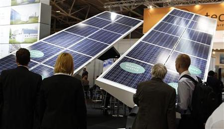 People watch photovoltaic (solar) panels during the 'Intersolar' Europe trade fair in Munich June 13, 2012. Around 1900 exhibitors will present their new technologies at the trade fair running until June 15, 2012. REUTERS/Michaela Rehle (GERMANY - Tags: BUSINESS ENERGY ENVIRONMENT SCIENCE TECHNOLOGY)