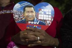 El mandatario venezolano, Hugo Chávez, es consciente de que su postoperatorio ha sido complejo, dijo el martes el vicepresidente Nicolás Maduro en una entrevista televisada desde Cuba, donde el líder socialista convalece tras una cuarta operación por el cáncer que padece. En la imagen, una partidaria de Chávez sostiene una foto suya durante una ceremonia en Caracas, el 31 de diciembre de 2012. REUTERS/Carlos Garcia Rawlins