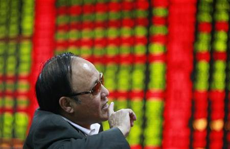 An investor gestures as he looks at an electronic board showing stock information at a brokerage house in Huaibei, Anhui province, October 25, 2012. REUTERS/Stringer/Files