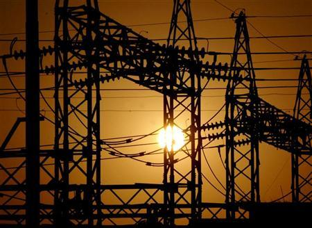 The sun sets behind electric pylons in Allahabad February 22, 2006. REUTERS/Jitendra Prakash/Files
