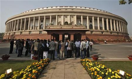 People stand in front of the Indian parliament building on the opening day of the winter session in New Delhi November 22, 2012. REUTERS/B Mathur/Files