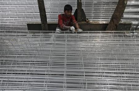 A worker paints sifts used for cement filtration at a manufacturing factory in the industrial area of Kolkata June 12, 2012. REUTERS/Rupak De Chowdhuri/Files