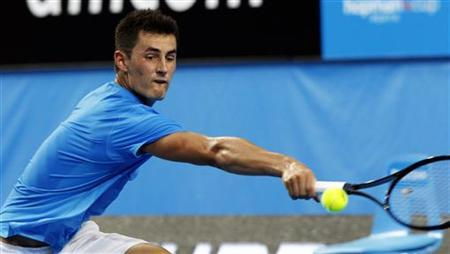 Bernard Tomic of Australia hits a return to Novak Djokovic of Serbia during their men's singles match at the Hopman Cup tennis tournament in Perth January 2, 2013. Djokovic suffered a shock loss to Tomic at the Hopman Cup team event on Wednesday, two weeks before the defence of his Australian Open title. REUTERS/Stringer