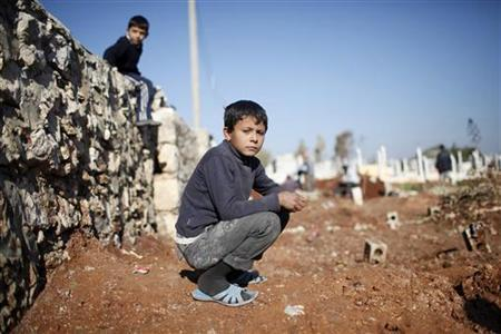 A child watches men dig graves for future casualties of Syria's civil conflict at Sheikh Saeed cemetery in Azaz city, north of Aleppo December 30, 2012. REUTERS/Ahmed Jadallah/Files