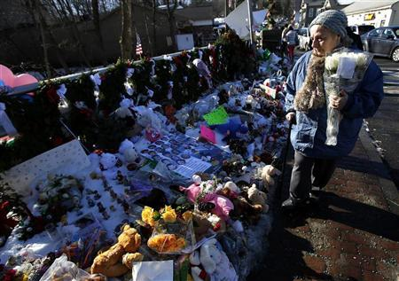 A woman with flowers walks past a makeshift memorial in Sandy Hook, after the December 14 shooting tragedy when a gunman shot dead 20 students and six adults at Sandy Hook Elementary, in Newtown, Connecticut, December 28, 2012. REUTERS/Carlo Allegri