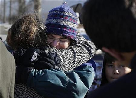 People hug at a makeshift memorial in Sandy Hook after the Dec.14 shooting tragedy when a gunman shot dead 20 students and six adults at Sandy Hook Elementary School, in Newtown, Connecticut, December 28, 2012. REUTERS/Carlo Allegri