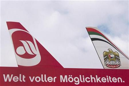 A billboard of carriers Air Berlin (L) and Etihad Airways is seen at Tegel Airport in Berlin December 18, 2012. Gulf carrier Etihad is buying a 70 percent stake in Air Berlin's frequent-flyer programme, injecting cash into the loss-making German airline as it struggles to return to profit. The writing reads, ''A world full of possibilities.'' REUTERS/Thomas Peter (GERMANY - Tags: BUSINESS TRANSPORT)