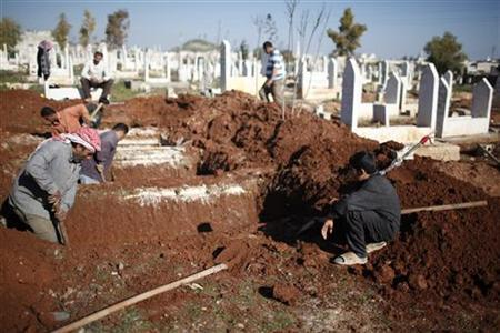 A boy watches men dig graves for future casualties of Syria's civil conflict, at Sheikh Saeed cemetery in Azaz city, north of Aleppo December 30, 2012. The international peace envoy for Syria said the situation in the country was deteriorating sharply but a solution was still possible under the terms of a peace plan agreed in Geneva in June. This conflict has killed at least 44,000 people since the start of an uprising against Syrian President Bashar al-Assad in March 2011. REUTERS/Ahmed Jadallah (SYRIA - Tags: CONFLICT)
