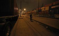 Homem passa por contêiners e caminhões esperando apra desembarcar suas cargas no Porto de Santos, no Brasil. O porto, principal do país, deverá registrar um novo recorde de movimentação de cargas em 2013, em 109 milhões de toneladas. 20/09/2012 REUTERS/Nacho Doce