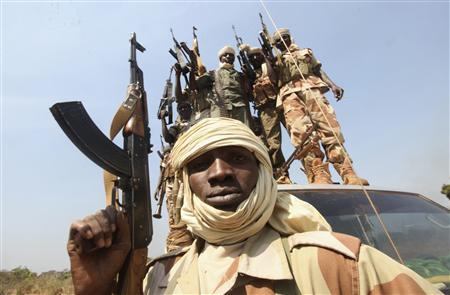 Soldiers from the Chadian contingent of the Central African Multinational Force (FOMAC) hold up their weapons in Damara, about 75 km (46 miles) north of Bangui January 2, 2013. Rebels in Central African Republic said they had halted their advance on the capital on Wednesday and agreed to start peace talks, averting a clash with regionally backed troops in the mineral-rich nation. REUTERS/Luc Gnago