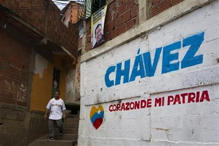 A man walks past a mural in Caracas January 2, 2013. The words read, ''Chavez, heart of my country''. REUTERS/Carlos Garcia Rawlins