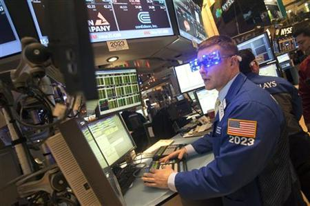 Trader Joseph Mastrolia wears ''2013'' glasses celebrating New Year's Eve as he works on the floor of the New York Stock Exchange in New York, December 31, 2012. REUTERS/Keith Bedford (