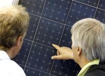 Las instalaciones de energía solar respaldadas por ayudas en Alemania desde enero a noviembre de 2012 indican que los datos de todo el año se acercan al récord del año pasado, poniendo de relieve los crecientes costes para los consumidores. En esta imagen de archivo, gente mirando paneles fotovoltaicos en la feria europea Intersolar, en Múnich, el 13 de junio de 2012. REUTERS/Michaela Rehle