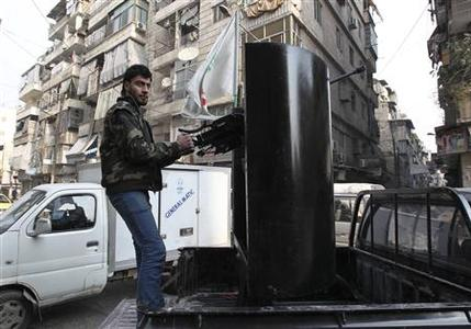 A member of the Free Syrian Army stands atop a truck while on patrol in Aleppo's Bustan Al Qaser district January 2, 2013. REUTERS/Muzaffar Salman