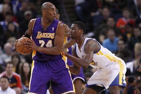 Los Angeles Lakers guard Kobe Bryant (L) looks for an opening as Golden State Warriors Harrison Barnes defends, during the first quarter of their NBA basketball game in Oakland, California December 22, 2012. REUTERS/Stephen Lam