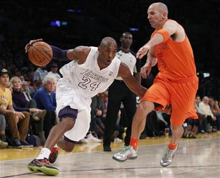 Los Angeles Lakers' Kobe Bryant (L) drives around New York Knicks' Jason Kidd (R) during the second half of their NBA basketball game in Los Angeles December 25, 2012. REUTERS/Danny Moloshok/Files