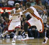 Miami Heat's LeBron James (L) prepares to pass to teammate Dwyane Wade in overtime against the Dallas Mavericks during their NBA basketball game in Miami, Florida January 2, 2013. REUTERS/Andrew Innerarity