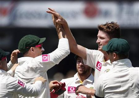Australia's Jackson Bird (R) congratulates teammate Mike Hussey (L) after they combined to dismiss Sri Lanka's Dimuth Karunaratne during the first day's play of the third cricket test match at the Sydney Cricket Ground January 3, 2013. REUTERS/Tim Wimborne
