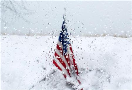 An American flag that is planted in the snowy ground REUTERS/Carlo Allegri (UNITED STATES - Tags: CRIME LAW OBITUARY)