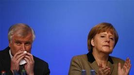 German Chancellor and leader of Germany's Christian Democratic Union (CDU), Angela Merkel sits next to sister party Christian Social Union (CSU) leader Horst Seehofer during the second day of the CDU's annual party meeting in Hanover, December 5, 2012. REUTERS/Kai Pfaffenbach (GERMANY - Tags: POLITICS)