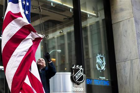 A worker lowers the U.S. flag outside of NHL headquarters in New York, January 2, 2013. REUTERS/Lucas Jackson