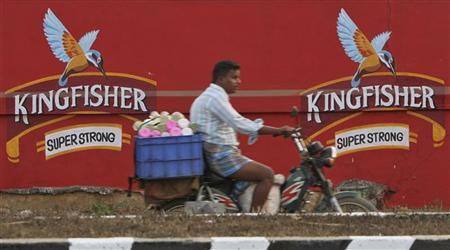 A man on a motorbike rides past the factory of United Breweries Ltd (UB) that manufactures Kingfisher beer in Thiruvalluar district of Tamil Nadu April 3, 2012. REUTERS/Babu/Files