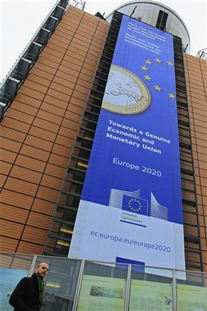 A banner featuring a Euro coin is seen on the European Commission headquarters building in Brussels November 21, 2012. REUTERS/Yves Herman (BELGIUM - Tags: POLITICS BUSINESS)