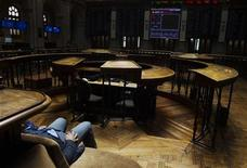 El Ibex-35 abrió con un ligero retroceso tras subir casi un 3,5 por ciento el miércoles por el alivio que sintieron los mercados internacionales por el acuerdo de última hora alcanzado por el congreso estadounidense que evitó el temido abismo fiscal. En la imagen de archivo, un hombre mira la pantalla principal de la Bolsa de Madrid, el 2 de agosto de 2012. REUTERS/Susana Vera