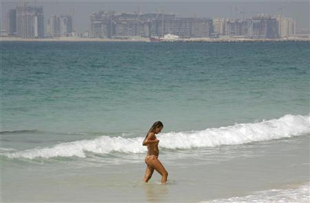 A swimmer walks on a beach in Jumeirah in Dubai in this picture taken September 23, 2008. REUTERS/Morteza Nikoubazl