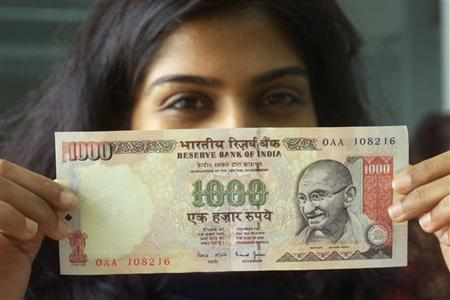 A girl displays a 1000 rupee note in Mumbai, October 11, 2000. REUTERS/Files